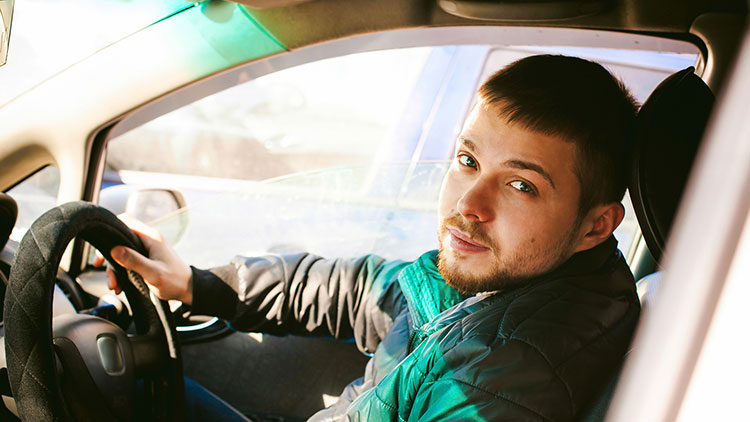 A young male driver in a car